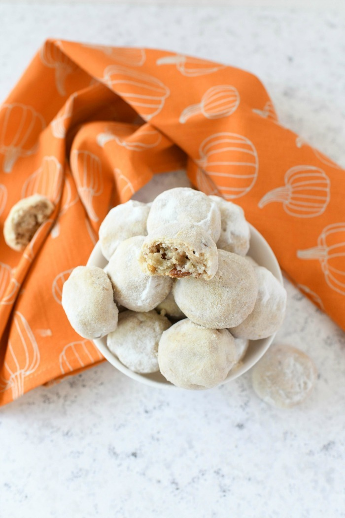 Pumpkin Snowball cookies in a white bowl with a bite taken out of one.
