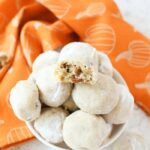 Pumpkin Spice snowball cookies in a white bowl with a pumpkin napkin.