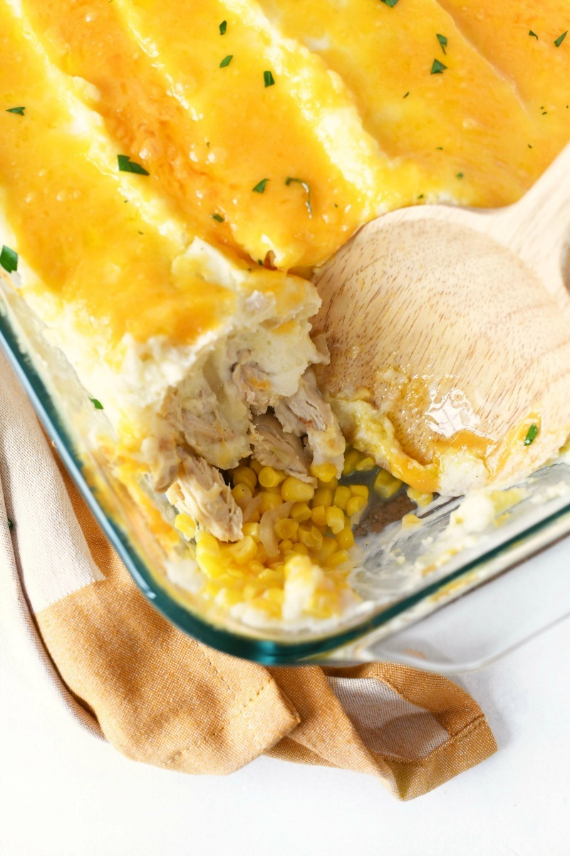 Turkey corn cheese casserole with a jumbo wooden spoon.