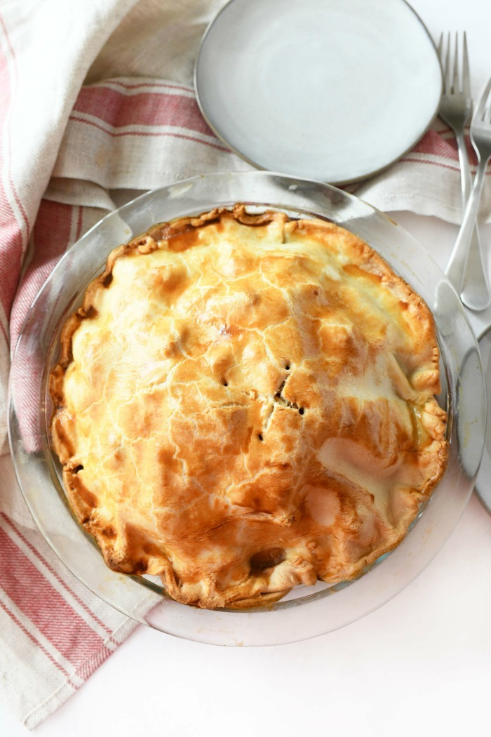 Golden-brown baked apple pie near a red and tan napkin.
