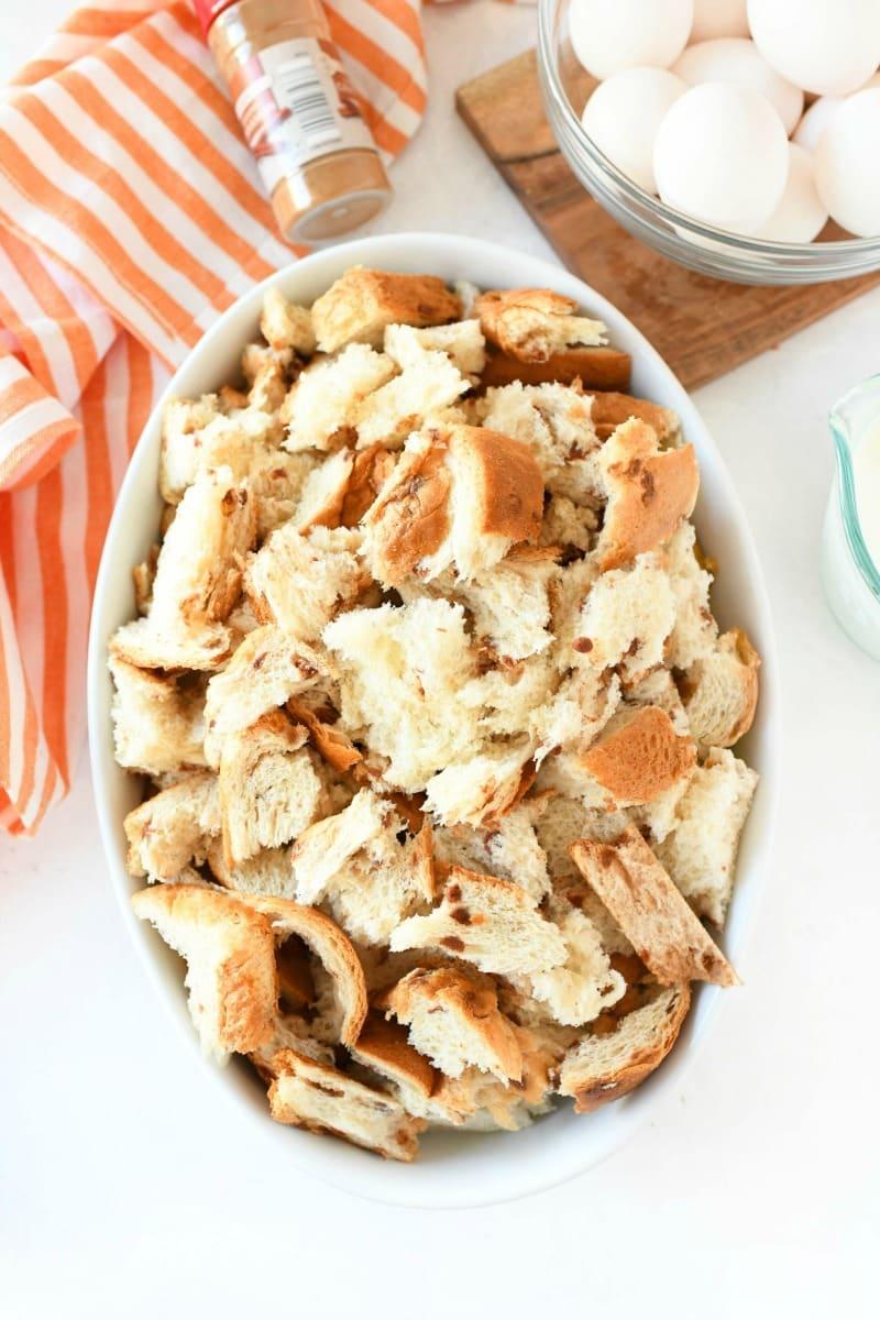 Broken cinnamon bread in a white oval casserole dish.