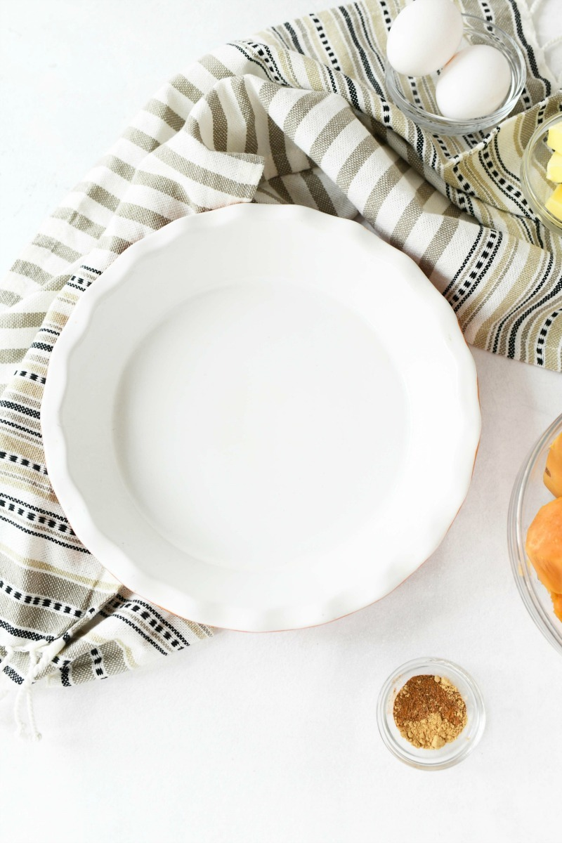 white pie dish with a striped napkin on a table.