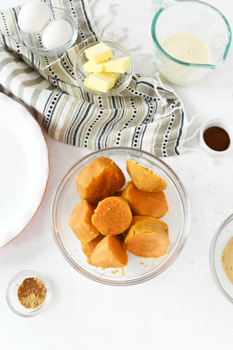 Steamed sweet potatoes in a glass dish on a white table.