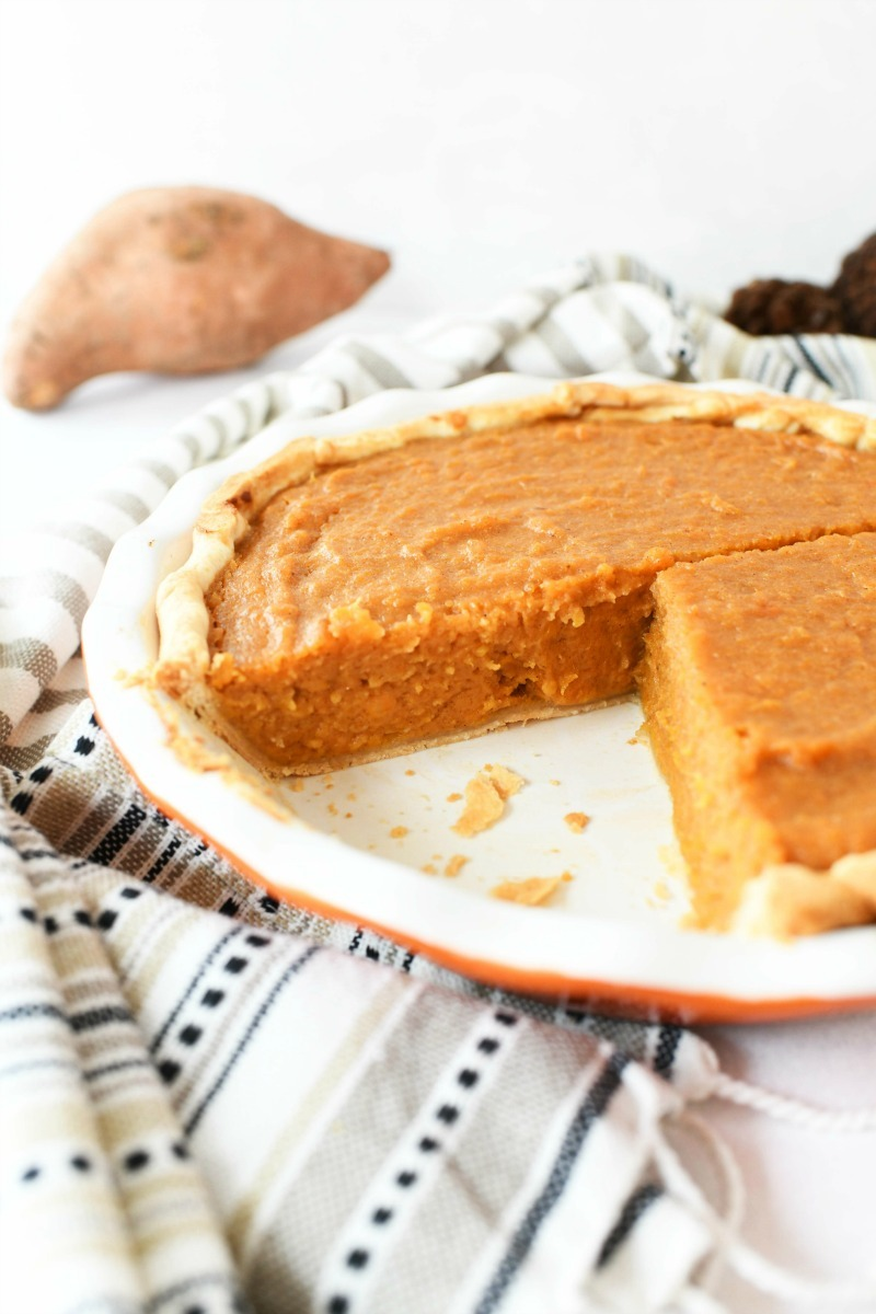 Sweet Potato Pie in a pie dish with a slice removed.