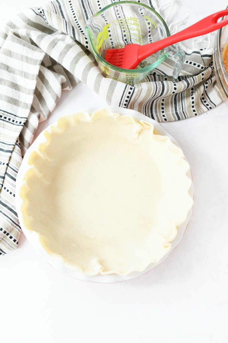 unbaked pie shell on a white table.