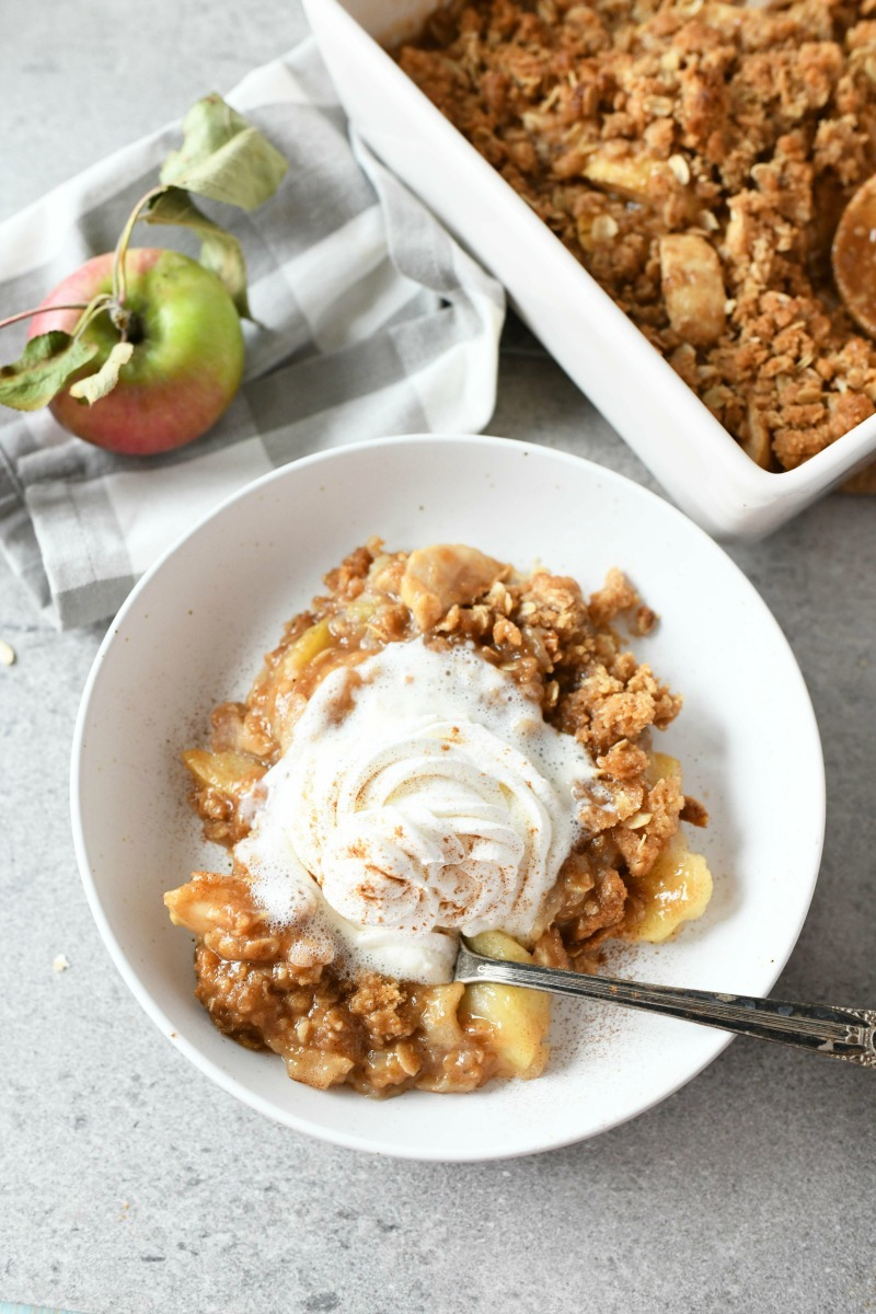 Apple Crisp with cream in a white dish with a spoon.