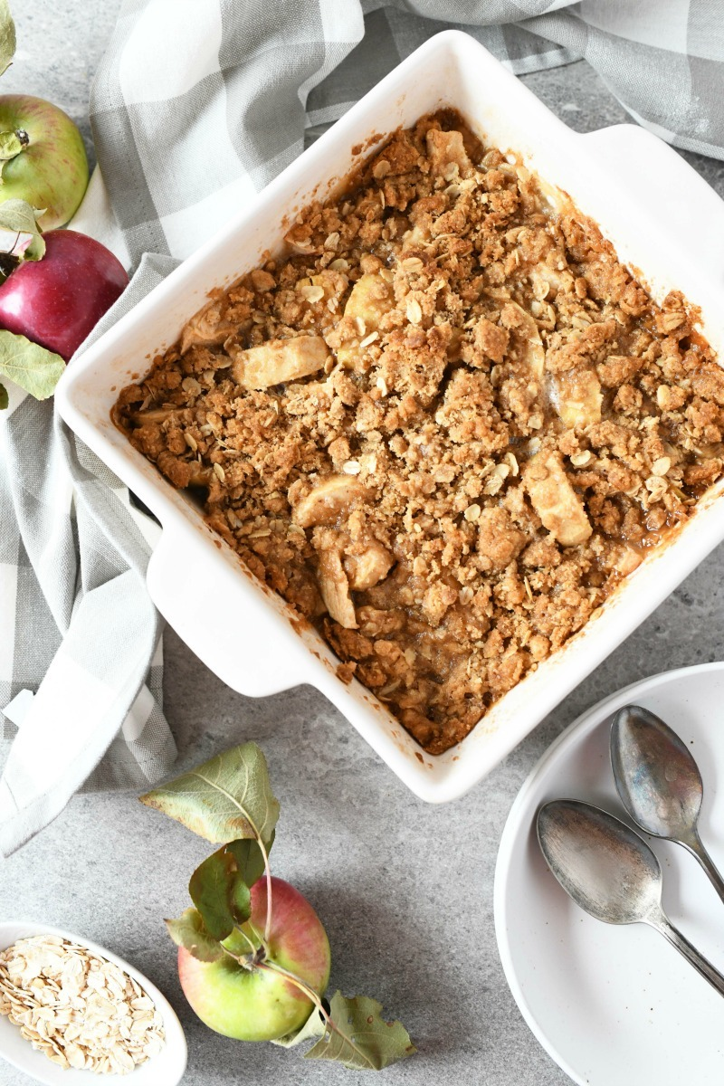 Baked Apple Crisp in a white square pan. It is styled near apples, and plates with spoons on a gray table.