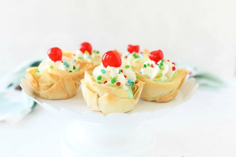 Phyllo Dough Cups with sprinkles and whipped cream on a white cake stand.