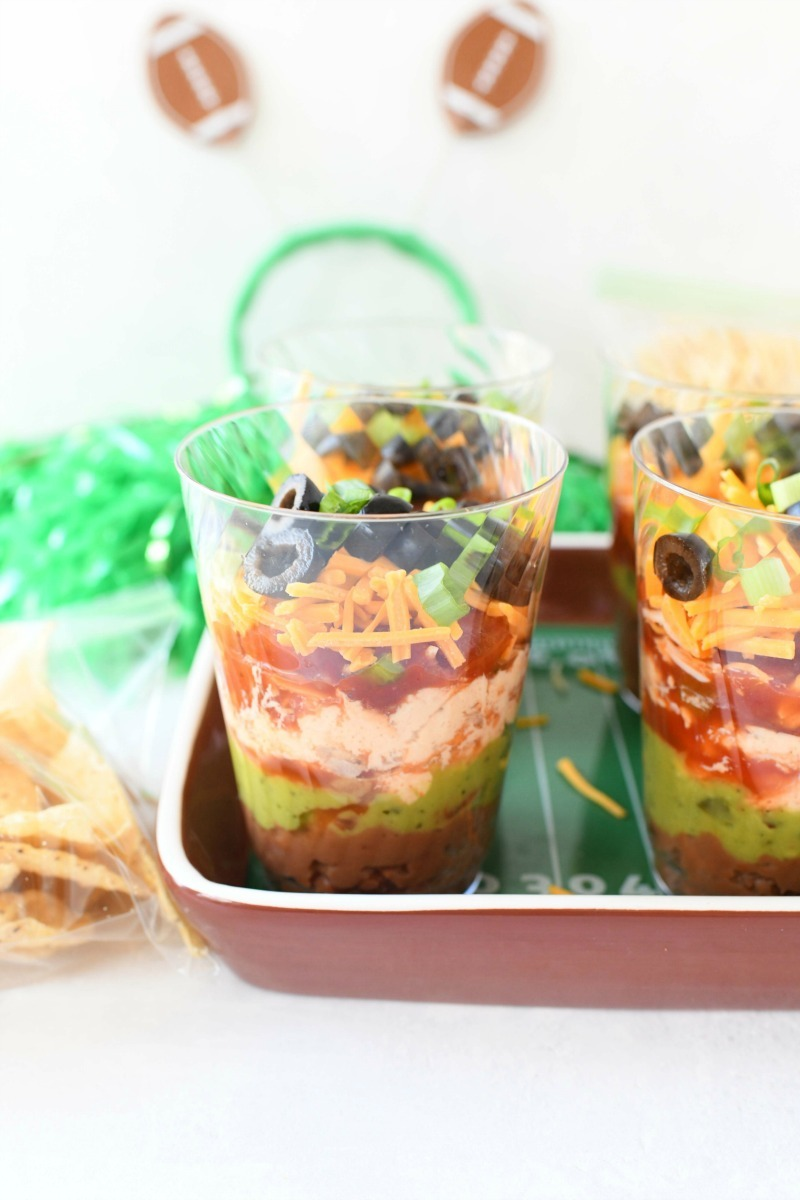 7-layer Dip with Tortilla chips on a brown football tray.