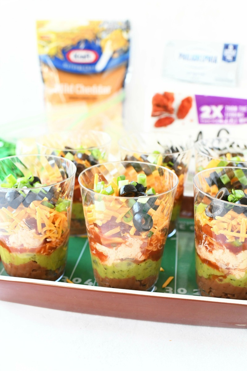 7 layer dip cups filled on a football tray.