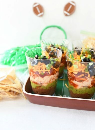 7 layer dip in small cups in a football tray.