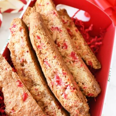 Almond Cherry Biscotti in a red baking box with red paper shreds.