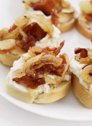 Caramelized Bacon Bites on a white plate with white paper napkins.