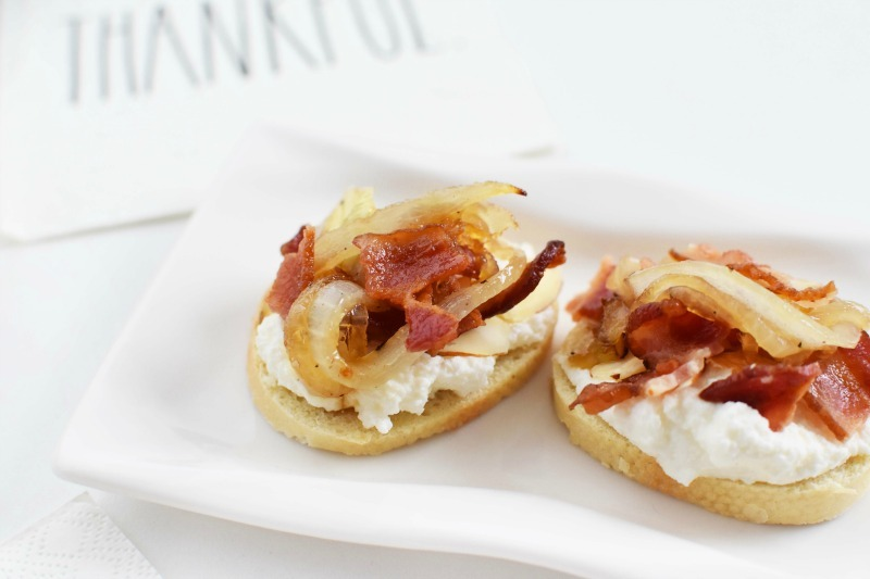 Caramelized Bacon & Onion Bites on a small rectangular plate. There is a paper napkin that says thankful in the background.