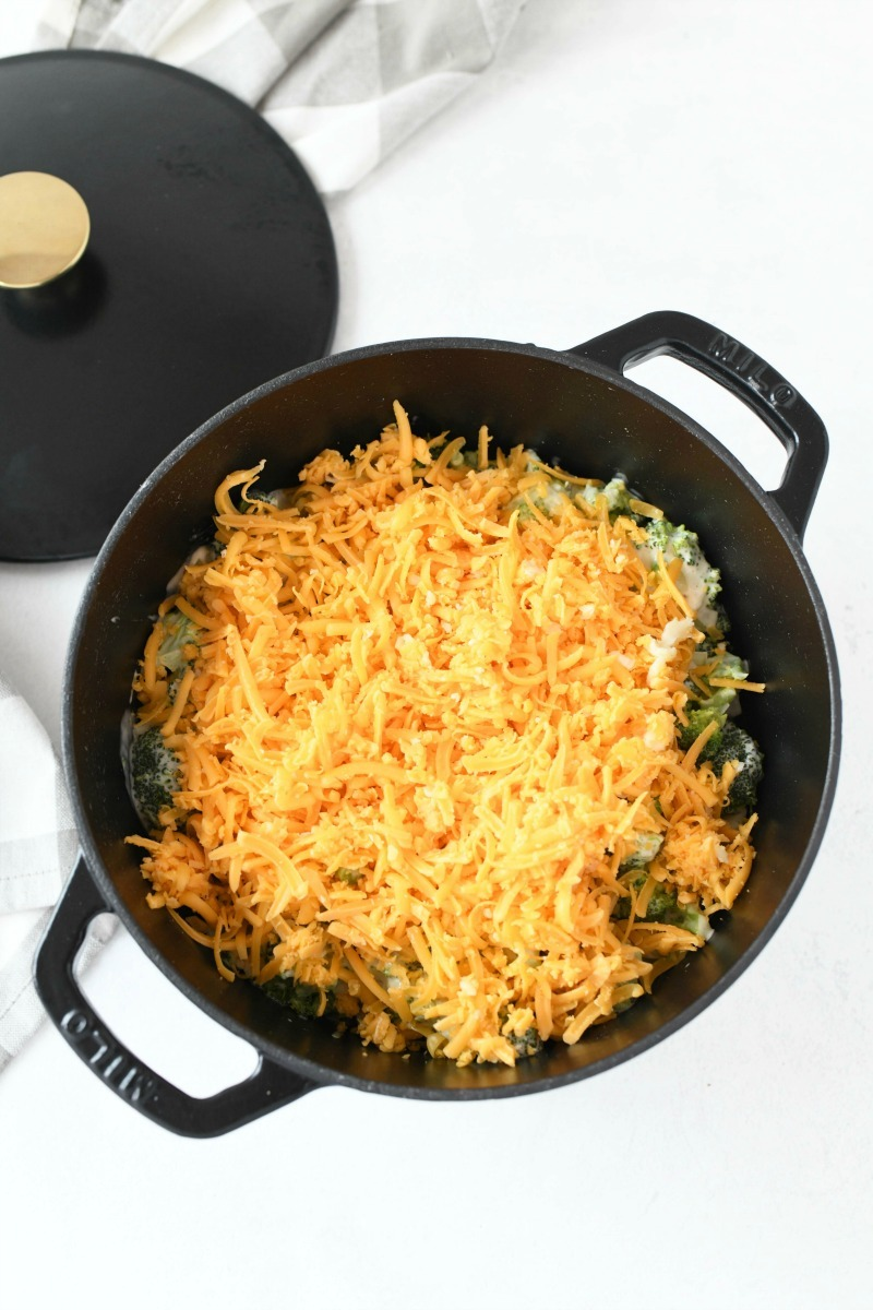 Cheese on Broccoli casserole unbaked in a black 3.5 quart casserole dish.