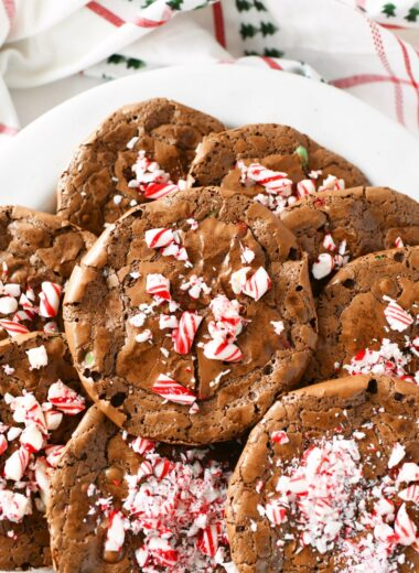 Chocolate peppermint cookies on a white plate with a Christmas napkin in the background.