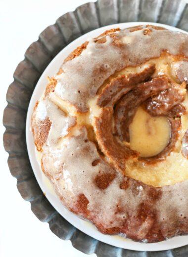 Eggnog Bundt Cake with eggnog glaze on a galvanized cake stand.