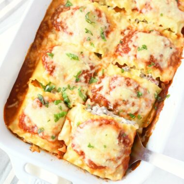 Lasagna rolls in a pan. These are baked and have a cheesy topping. They are baked in a white rectangle pan, and there is a white napkin nearby.