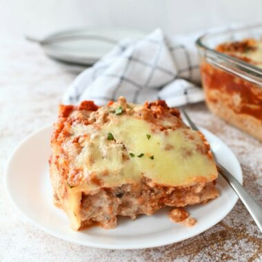 Meat and Cheese Lasagna Slice on a white small dish with a silver fork.