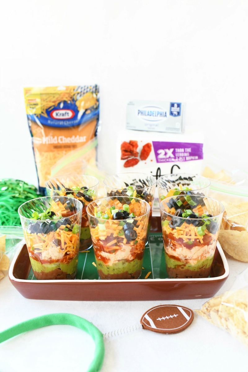 Mexican 7-layer dip cups with kraft cheese and vanity fair napkins on the table. There is also a football headband there.