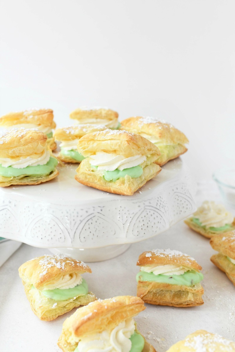 Pistachio Cream Puffs on a white table with a white cake stand.