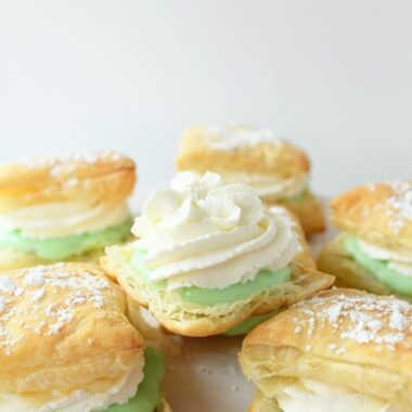 Pistachio Cream Puffs stacked on top of each other on a white cake stand.