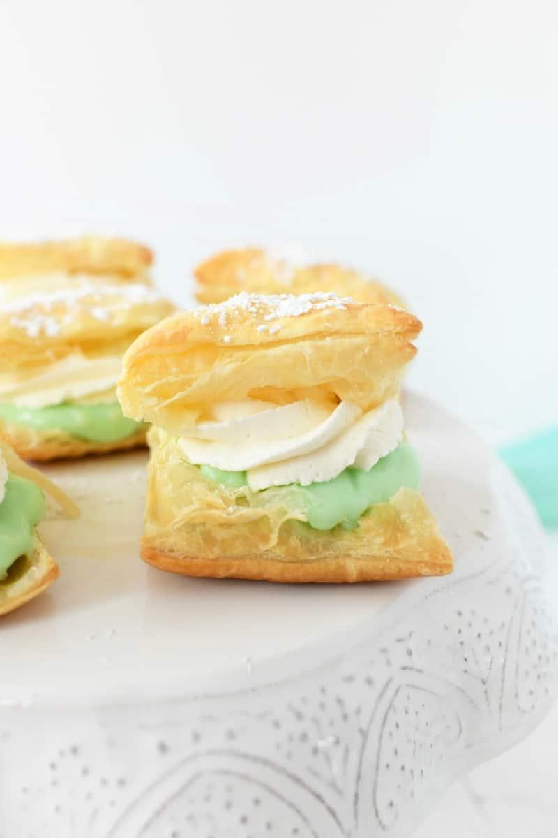 Pistachio pudding cream puff on a white cake stand.