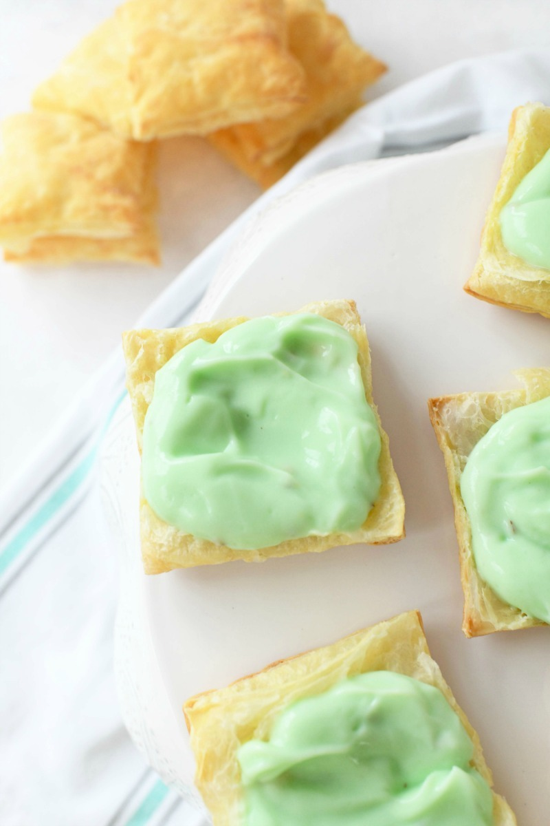 Pistachio pudding on puff pastry squares on a white cake stand.