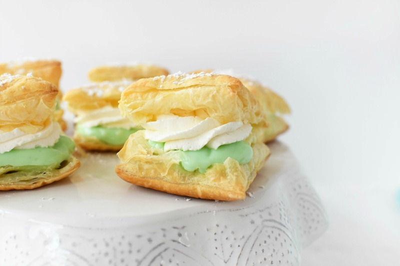 Pistachio pudding puffs on a white cake stand.