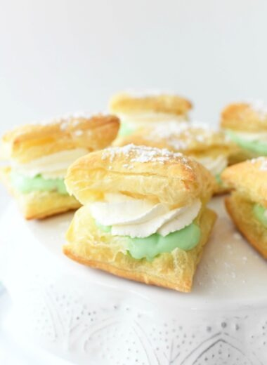 Pistachio puffs assembled on a white cake stand.