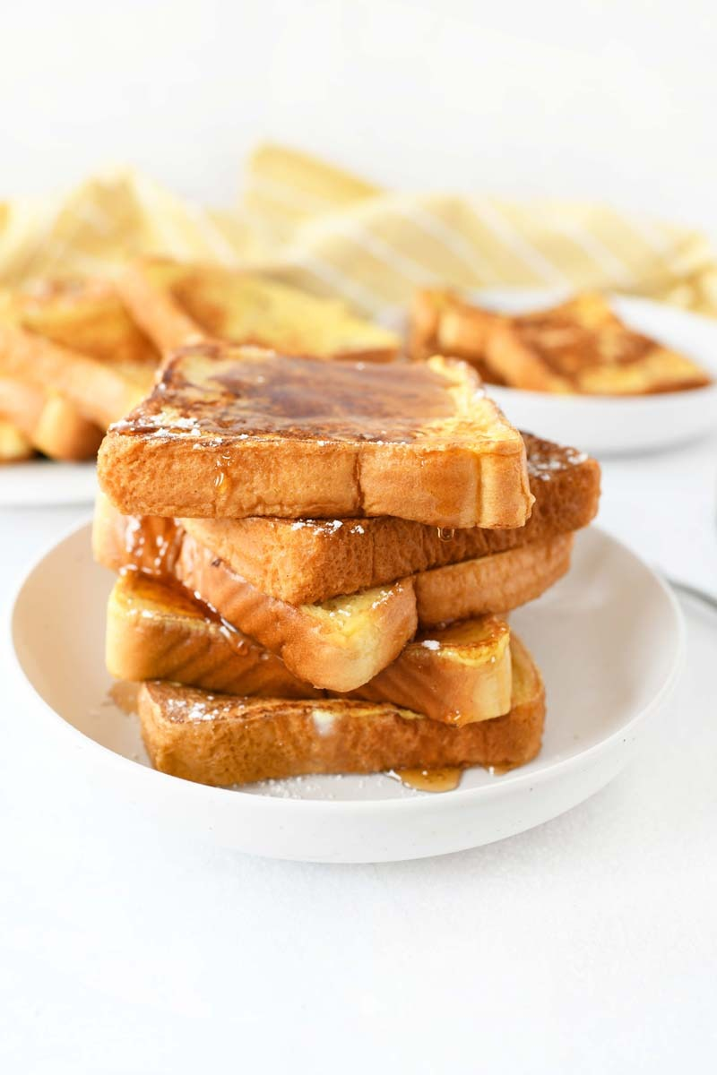 Almond Milk French Toast with Syrup on a white plate with syrup on top of it.