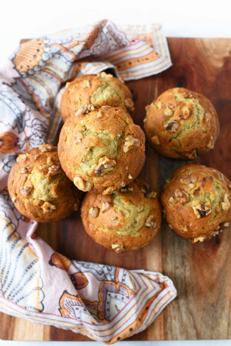 Bakery Style Banana Nut Muffins on a wooden board with a pink, floral napkin. There are 6 jumbo muffins in this shot.