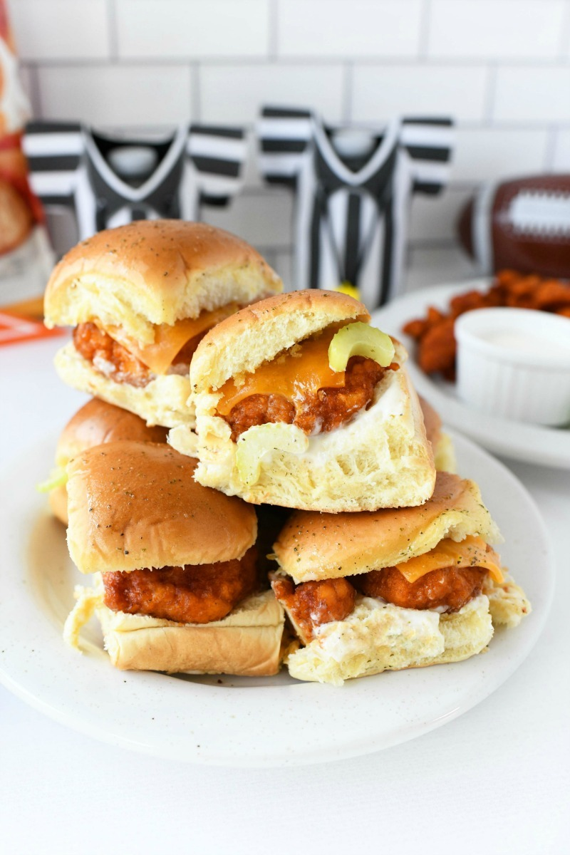 Buffalo Chicken Sliders are stacked on a white plate. There are black and white cozies in the background.
