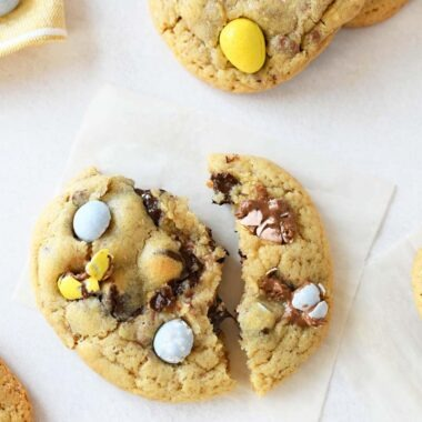 Cadbury Egg Cookies are stretched open on a square of parchment paper. The cookies is warm and inviting with other cookies and a yellow napkin in the background.
