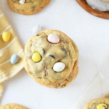 Cadbury Egg cookies with chocolate chips are stacked. The shot is top down and show a peep of a yellow striped napkin on the left side.