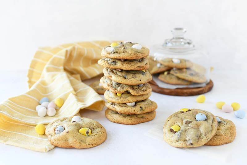 Chewy Cadbury Chocolate Chip Cookies are stacked 7 high. There is a little dessert holder, and yellow napkin in the background with egg candies scattered.