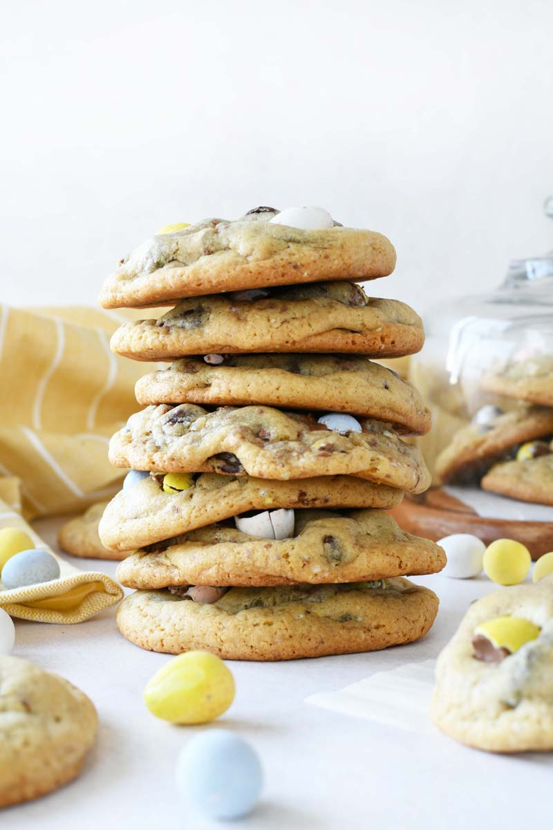 Chewy Cadbury Egg cookies are stacked 7 cookies high. There are cookies, candy eggs, and a yellow napkin in the background of the image.
