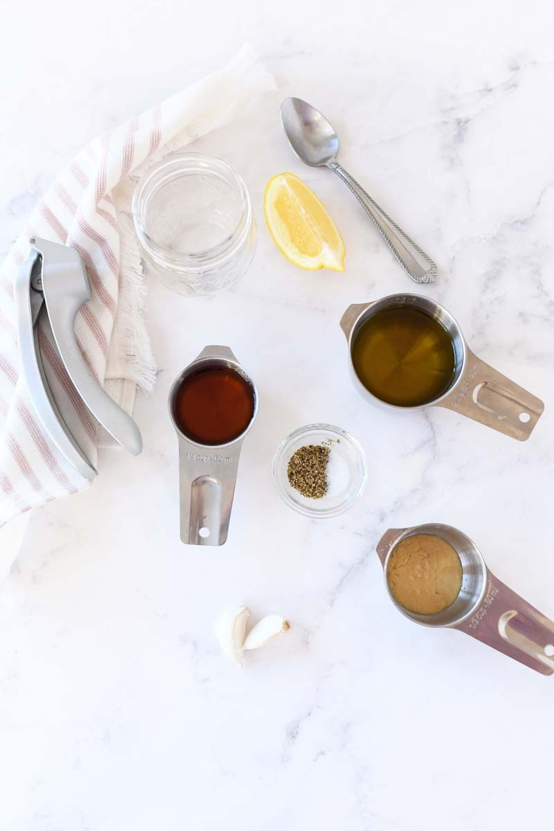Greek Dressing Ingredients on a white marble table. The ingredients are in stainless steel containers.
