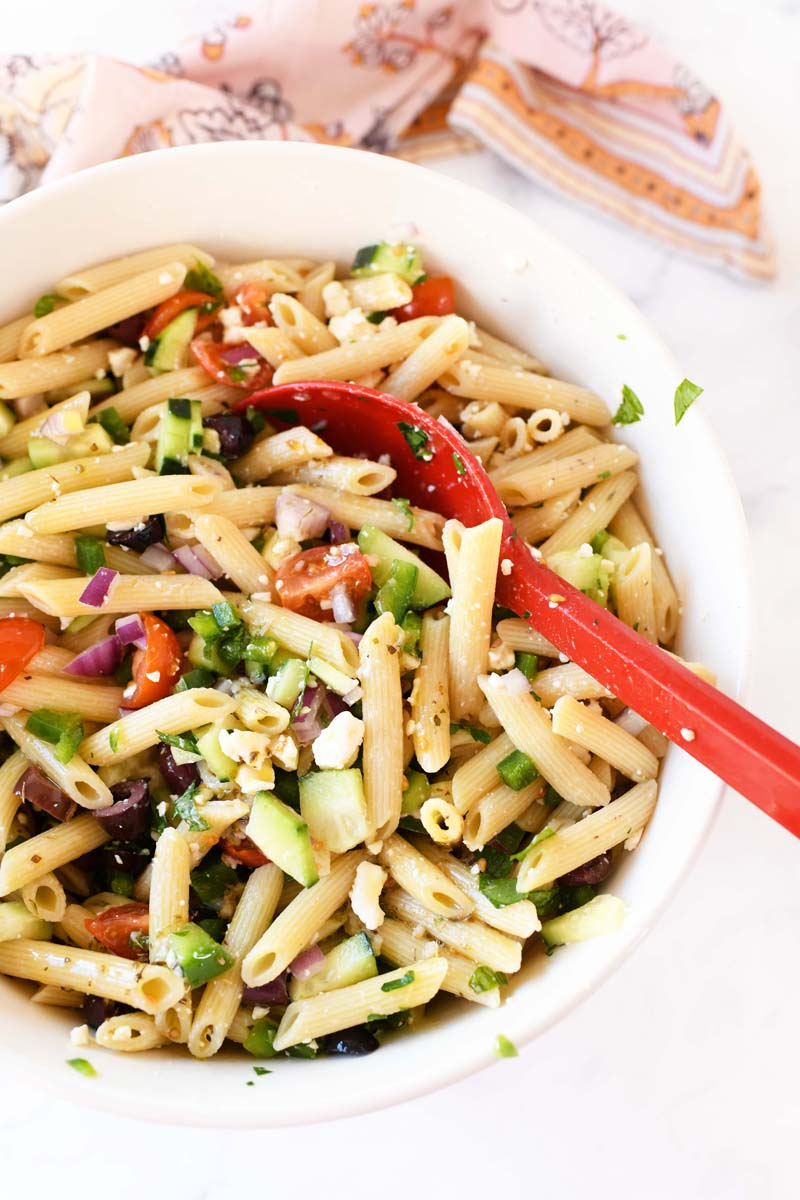 Greek Pasta Salad Recipe in a white bowl with a red spoon. There is a patterned napkin in the background.