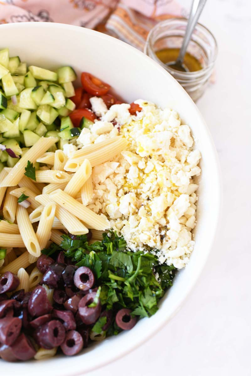 Greek Pasta Salad ingredients with a splash of dressing on them in a large white bowl. There is a jar of dressing and a pink, patterned napkin nearby.