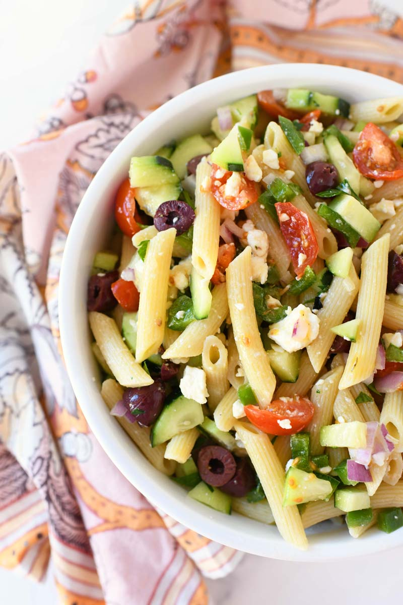 Greek Penne Pasta Salad in a white dish with a pink patterned napkin.