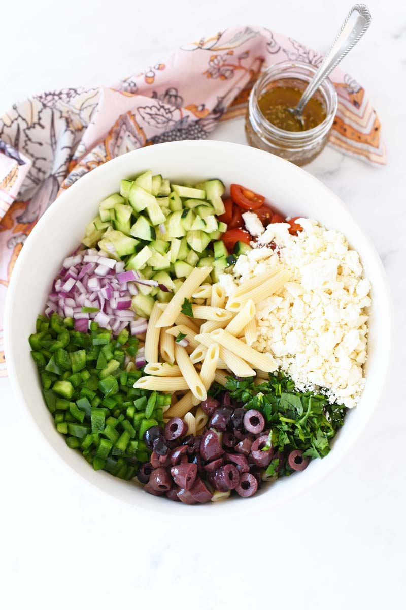 Greek Salad ingredients in a large white bowl with a jar of house dressing nearby.