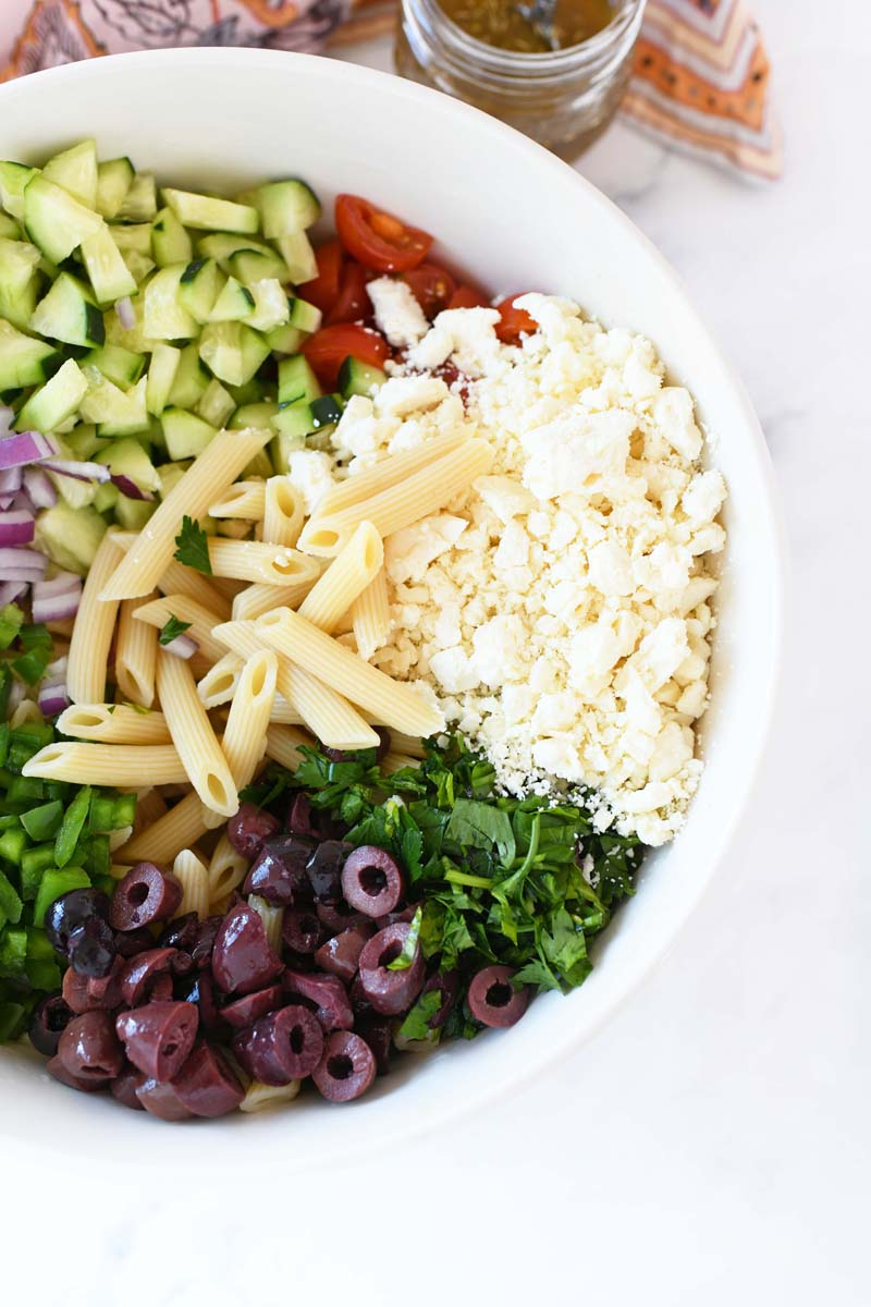 Greek pasta salad ingredients in a small, white bowl.