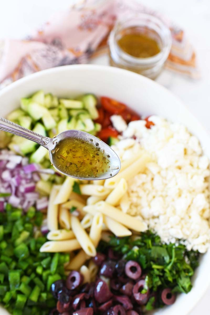 Homemade Greek Dressing in a spoon. A Greek pasta salad is in the background.