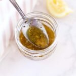 Homemade Greek Dressing in a jar with a spoon in it. There is a squeezed lemon nearby.