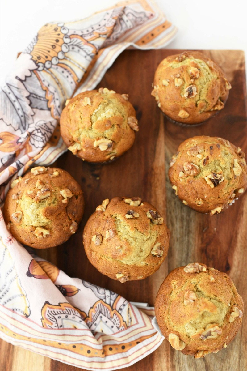 Jumbo Banana Nut Muffins. There are 6 muffins on a wooden plank with a pink, floral napkin nearby.