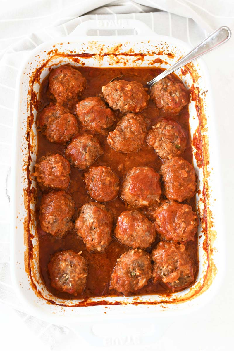 Porcupine Meatballs in tomato sauce. They are inside a white rectangle casserole dish.