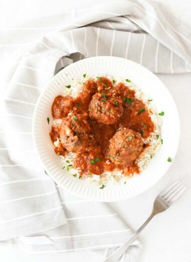 Porcupine meatballs in a plate on a white table. There is a grey napkin, and fork nearby.