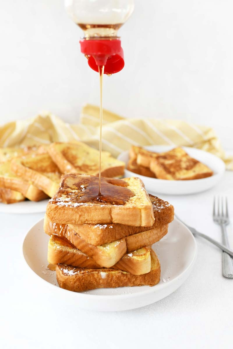 Syrup pouring on French toast. Toast is on white plates.