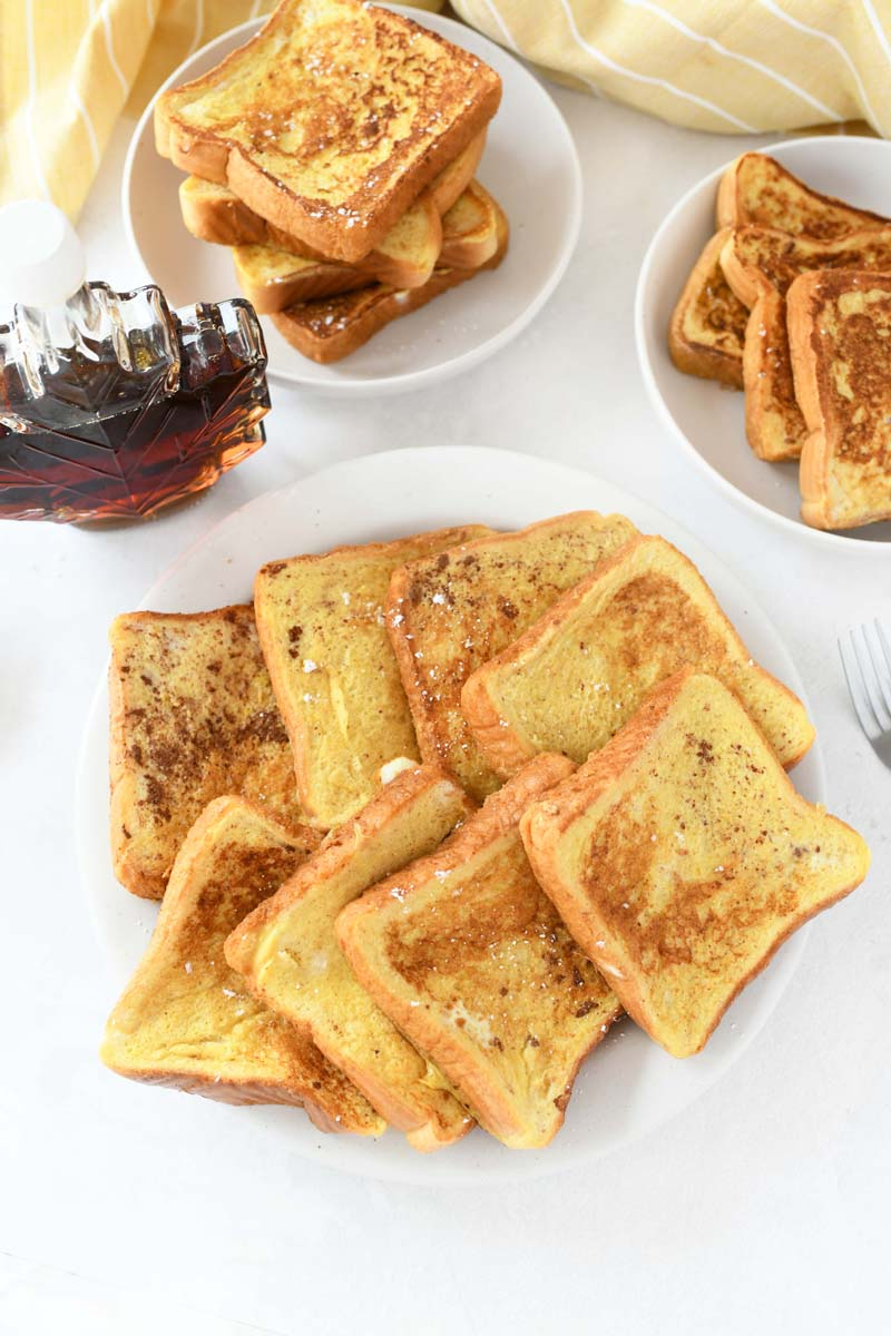 Thick French toast made with almond milk. French toast is on plates with a maple leaf syrup bottle nearby.